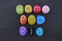 Homophobia word composed with multi colored stones over black volcanic sand. Multi colored word, Homophobia composed over natural black volcanic sand stock photo