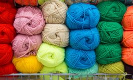 Multi-colored yarn. Yarn is beige, brown, grey and white. Knitting needles, scissors, coffee, knitting, knitted fabric. stock photo