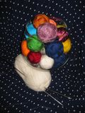 Multi-colored yarn lying in a transparent glass vase on a background of black fabric with white dots. Against the background of black fabric in white polka dots Stock Images
