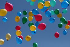 Multi-coloured balloons depart to the sky. Holiday Stock Photo
