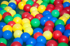 Multi-coloured balls float on water Royalty Free Stock Photo