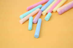 Multi coloured chalk sticks. On a yellow background. With shallow focus Royalty Free Stock Photography