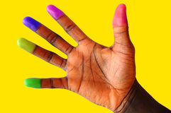 Multi coloured (cultured) finger tips 2. This is an image of a black hand with various different coloured finger tips. Gold background stock images