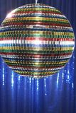 Multi-coloured disco ball in front of blue stage curtain close up Royalty Free Stock Photos