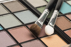 Multi coloured eye shadow palette with brushes Stock Photos
