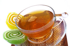 Multi-coloured fruit candy and cup  of tea Stock Image