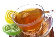 Multi-coloured fruitsuikergoed en kop thee Stock Afbeelding