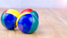 Multi-Coloured juggle balls on wooden surface Royalty Free Stock Photography