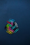 Multi coloured paper clips on plain background. Multi coloured paper clips on plain black background stock image