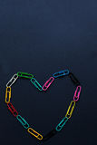 Multi coloured paper clips in the shape of a heart on plain back royalty free stock photos