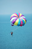 Multi coloured parachut e over the blue sky. Multi coloured parachute over the blue sky Royalty Free Stock Images