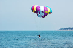 Multi coloured parachute. Over the blue sky Royalty Free Stock Photo