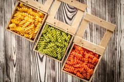 Multi-coloured pasta in the form of spirals lies in square wooden boxes that stand on a table. Multi-coloured pasta in the form of spirals lies in square wooden stock images