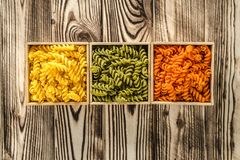 Multi-coloured pasta in the form of spirals lies in square wooden boxes that stand on a table. Multi-coloured pasta in the form of spirals lies in square wooden royalty free stock image