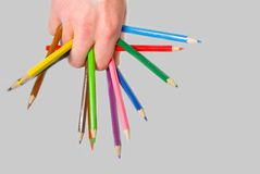 Multi-coloured pencils. The set of multi-coloured pencils is placed on a hand arbitrarily Stock Photography