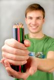 Multi-coloured pencils. Young guy holds  set of multi-coloured pencils in hands Stock Photos
