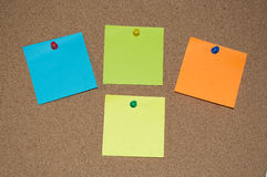 Multi Coloured Post it Notes on a Cork Board Royalty Free Stock Photos