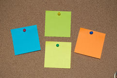 Multi Coloured Post it Notes on a Cork Board. Four Multi Coloured Post it Notes on a Cork Board stock image
