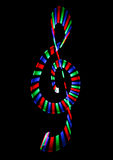 Multi-coloured shone treble clef on black Royalty Free Stock Images