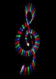 Multi-coloured shone treble clef on black. Background. Musical symbol royalty free illustration