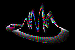 Multi-coloured wavy trace of light-emitting diode. On black background Stock Photography
