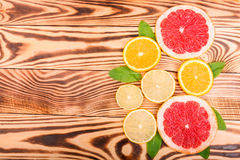 Multi-colourful slices of fresh orange, juicy lemon and ripe grapefruit with green leaves on a light brown wooden table, top view. Stock Photo