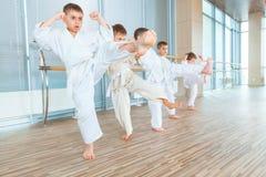 Multi crianças éticas novas, bonitas, bem sucedidas na posição do karaté foto de stock royalty free