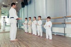 Multi crianças éticas novas, bonitas, bem sucedidas na posição do karaté Fotografia de Stock Royalty Free