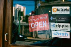 Multi Crypto Currencies welcome banner with text. `accepted here ` in front of door store, bitcoin, ethereum, ripple, dash coin stock photography