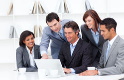 Multi-cultural business team looking at a laptop Royalty Free Stock Image