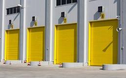 Multi-Door Garage. Four yellow garage doors for high industial cargo trucks Stock Photos