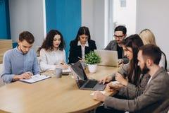 Multi empresário étnico dos povos, conceito da empresa de pequeno porte Mulher que mostra a colegas de trabalho algo no laptop co foto de stock royalty free