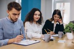 Multi empresário étnico dos povos, conceito da empresa de pequeno porte Mulher que mostra a colegas de trabalho algo no laptop co imagem de stock