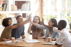 A multi equipe étnica feliz do negócio junta-se às mãos que dão altamente cinco fotos de stock