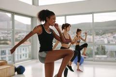 Multi esercizi etnici delle donne nella classe della palestra Immagine Stock