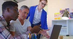 Multi-ethinic colegas do negócio que discutem sobre o portátil no escritório moderno 4k video estoque