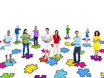 Multi-Ethinic People Standing On Jigsaw Puzzle Pieces Royalty Free Stock Image