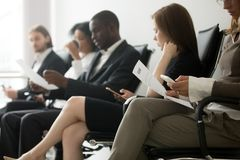 Multi-ethnic applicants sitting in queue waiting for job intervi. Multi-ethnic applicants sitting in queue preparing for interview, black and white vacancy royalty free stock image