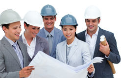 Multi-ethnic architects studying blueprints stock images