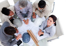 Multi-ethnic architects studying blueprints. High angle of multi-ethnic architects studying blueprints in a meeting Stock Photography