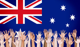 Multi-Ethnic Arms Raised and Australian Flag Background.  Stock Photos
