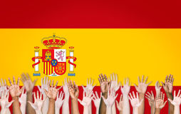 Multi-Ethnic Arms Raised and a Flag of Spain Royalty Free Stock Photos