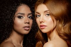 Multi-ethnic beauty. Caucasian and African. Different ethnicity women on black background. Beautiful vogue girls