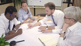 Multi-ethnic building team working together on house blueprint. stock video footage