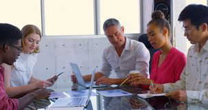 Multi-ethnic business colleagues discussing over graphs in a meeting at moder office 4k. Side view of multi-ethnic business colleagues discussing over graphs in stock footage
