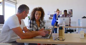 Multi-ethnic business colleagues discussing over laptop in modern office 4 4k. Side view of multi-ethnic business colleagues discussing over laptop in modern stock footage