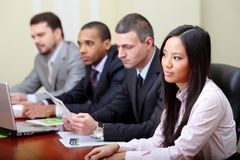 Multi ethnic business group. Multi ethnic business executives working with documents. Focus on woman royalty free stock image