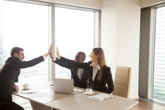 Multi-ethnic business partners giving high five on meeting, cele royalty free stock image