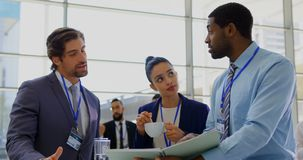 Multi ethnic business people discussing over a file during a seminar 4k. Front view of multi ethnic business people discussing over a file and handshaking each stock video