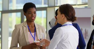 Multi ethnic business people interacting with each other at table during a seminar 4k. Multi ethnic business people holding a coffee or a glass of water while stock footage